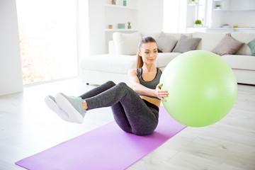 Beauty power legs sport clothing hobby day dream sofa domestic healthy lifestyle concept. Close up view photo of beautiful attractive pretty cheerful satisfied lady using ball for doing exercises