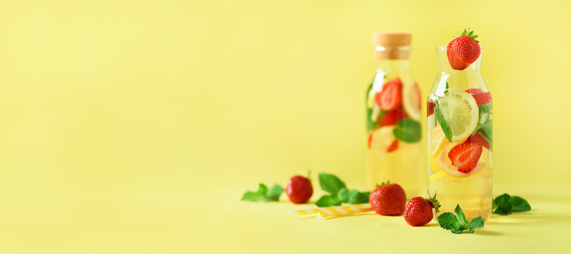 Strawberry detox water with mint, lemon on yellow background. Citrus lemonade. Banner. Summer fruit infused water. Copy space