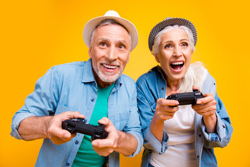 Grandfather grandmother jeans stylish cloth outfit concept. Close up photo portrait of shouting comic comedian trendy noisy wife and husband enjoying game holding wireless joystick isolated background