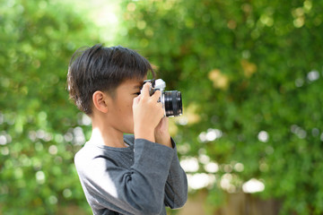 Young boy take photo by old camera