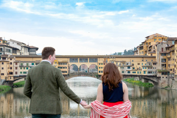 Young couple looking at Ponte Vecchio, the Old Bridge, Florence, Toscana, Italy