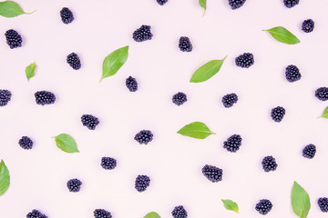 .Black delicious blackberries on a peach background with green basil leaves.