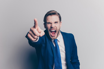 Portrait of violent, stylish, attractive, angry man in blue suit, tie with bristle, hairstyle, gesture, showing index finger front, yelling with wide open mouth, isolated on grey background