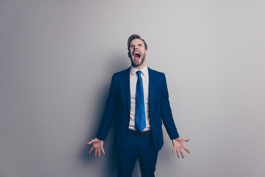Fail! Portrait of violent, stylish, attractive, angry man in blue suit, tie with bristle, hairstyle, yelling loud with wide open mouth, gesture palms, isolated on grey background