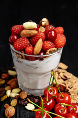 homemade yoghurt with flakes, nuts and berries of raspberries and cherries on dark wooden background