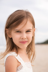 Close up portrait of cute little girl on the beach