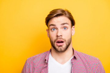 Close up portrait of handsome excited cheerful joyful attractive amazed funny with big eyes entrepreneur wearing red checkered shirt and white t-shirt isolated on bright yellow background copyspace
