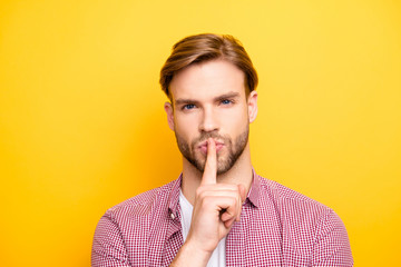 Close up portrait of confident pensive dreamy handsome sexy guy with stylish modern hairdo holding forefinger near mouth asking to be quiet isolated on bright yellow background copy-space Wall mural
