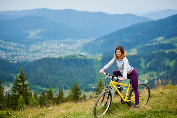 Side view of woman cyclist riding on yellow bicycle on the mountain range. Outdoor sport activity, lifestyle concept. Copy space