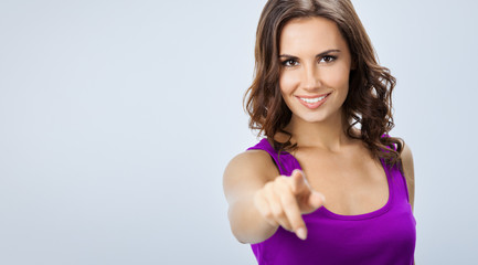 Woman pointing at something or pressing virual button, over grey