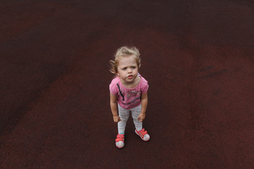 capricious little girl on a dark red background