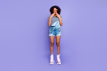 Oops! Portrait of impressed frustrated girl in eyewear riding on pink roller skates holding two hands near mouth isolated on bright violent background retro vintage student concept