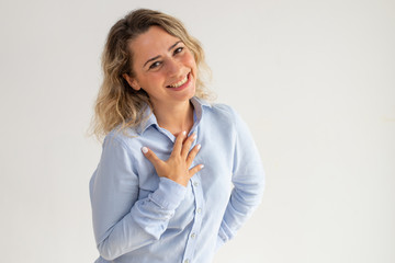 Cheerful thankful young woman honored and embarrassed. Happy curly-haired woman in blue blouse thanking and holding hand on chest. Respect concept