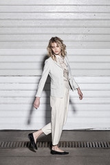 Full length fashion portrait of a woman standing against a wall on street. Street style