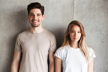 Portrait of young caucasian people man and woman in basic clothing posing together at camera with happy smile, isolated over concrete gray wall indoor