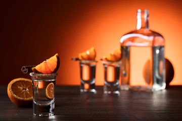 Glasses of tequila with orange and cinnamon sticks on a wooden table.