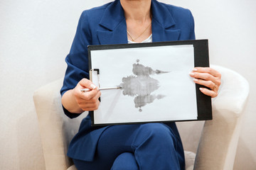 Woman is sitting and holding a picture. It is hand drawing. It is attached to the tablet. Woman is pointing on picture with pen.