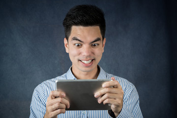 Close up handsome young asian man wearing a blue shirt  holding smart phone or tablet smile and looking isolated on gray background. Asian man people.  business success concept.