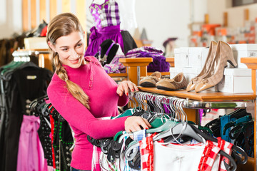 Traditional clothes - young woman is buying Tracht or dirndl in a shop