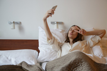 Young woman in the bed using smart phone, taking selfie photo