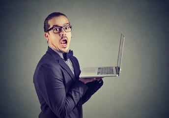 Shocked funny man reading news on laptop