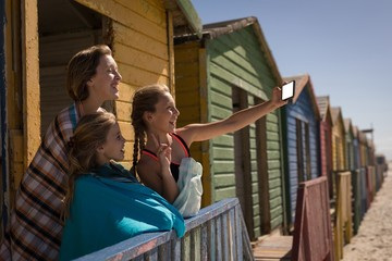 Siblings taking selfie with mobile phone at beach