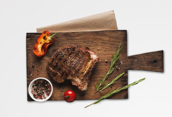 Grilled meat and vegetables on wooden board, isolated