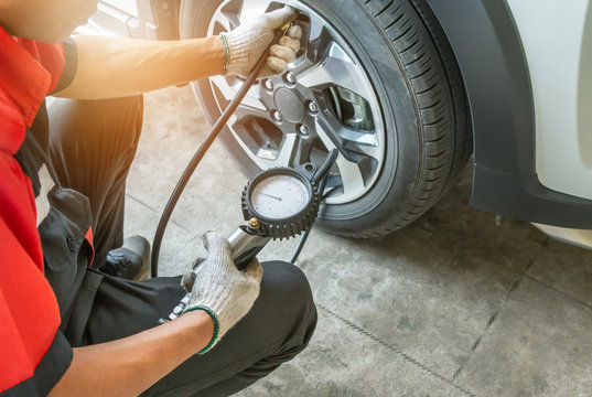 Close up mechanic inflating tire and checking air pressure with gauge pressure in service station