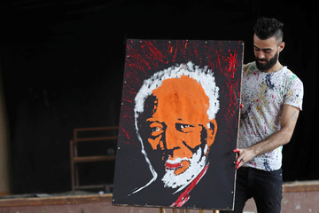Egyptian speed painter Albert Magdy holds the finished painting of American actor Morgan Freeman in Cairo