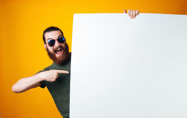 Excited bearded man wearing sunglasses is hiding behind and pointing at white blank sheet on yellow background.