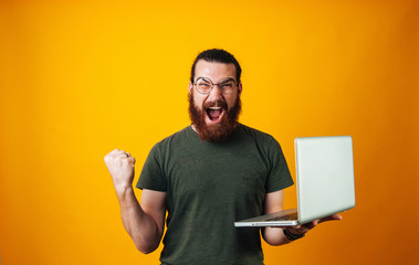 Winner bearded man wearing glasses and looking at the camera holding his notebook and making a winner gesture.