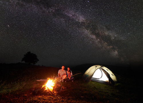 Modern tourist family camping in mountains by night. Husband and wife with small daughter sitting on a log in front of tent at burning campfire and look in camera. Tourism and traveling concept.