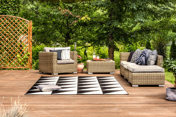 Geometrical rug and rattan furniture set on a terrace in a garden full of trees