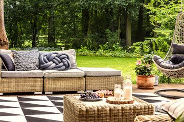 Milk and grapes on a table, sofa with knot pillow and geometrical carpet on a terrace in spa