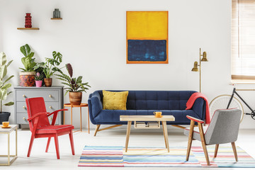 Red armchair next to wooden table and blue sofa in living room interior with painting. Real photo