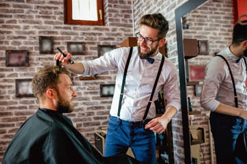 Hairdresser adjusts hair a customer with a comb