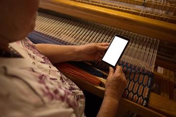 Senior woman using mobile phone in shop
