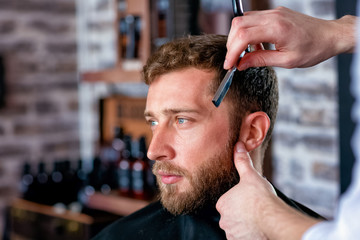 Hairdresser shaves man's beard with a blade