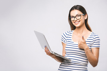 Portrait of happy young beautiful smiling woman standing with laptop isolated on white background. Space for text.