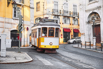 Lisbon, Portugal. Vintage yellow retro tram on narrow bystreet