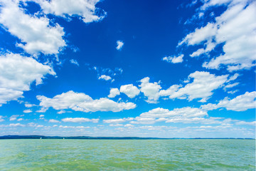 Summer green water lake with cloudy blue sky