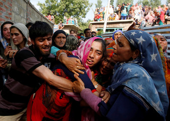 A woman mourns as she watches the body of Tamsheel Ahmad Khan, a civilian who according to local media died during clashes between protesters and Indian security forces, during his funeral at Vehil village in Kashmir's Shopian district