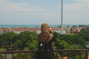 A muslim woman taking picture of Melaka city panorama with ocean in the background, Malaysia