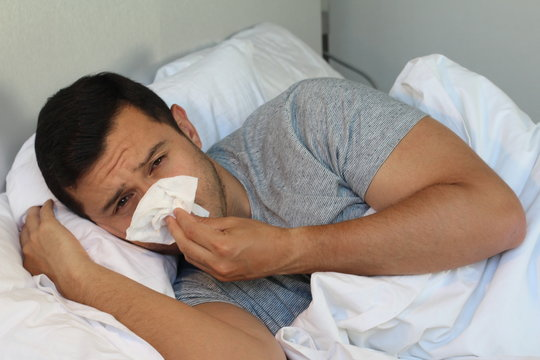 Man going through the flu in bed