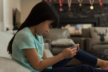 Girl using mobile phone in living room
