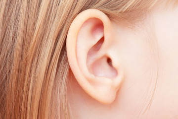 The little girl's ear is close-up. Isolated on white background. Wall mural