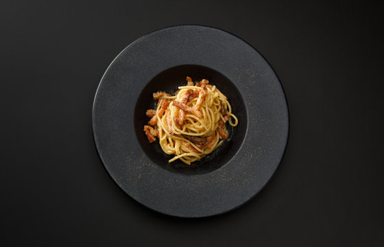 pasta carbonara with bacon in a black plate isolated on a black background