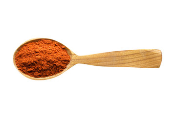 Fototapete - chili powder in wooden spoon isolated on white background. spice for cooking food, top view.