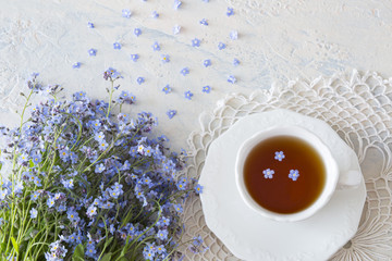 bouquet of flowers forget me nots and tea  on a light table