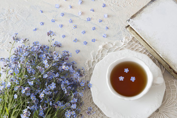 a bouquet of flowers forget-me-nots on a light table and a cup of tea and a book